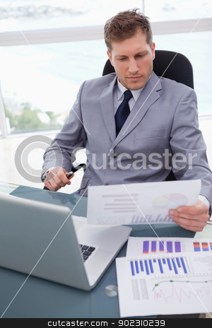 Businessman with market research results leaning back stock photo, Businessman with market research results leaning back in his chair by Wavebreak Media