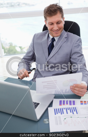 Smiling businessman looking at market research results stock photo, Smiling businessman at his desk looking at market research results by Wavebreak Media