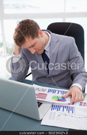 Businessman frustrated by market research results stock photo, Businessman at his desk frustrated by market research results by Wavebreak Media
