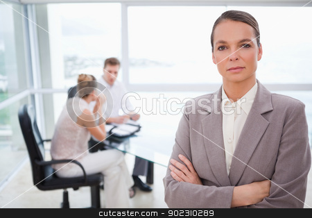 Consultant standing with folded arms stock photo, Consultant standing with folded arms and sitting customers behind her by Wavebreak Media