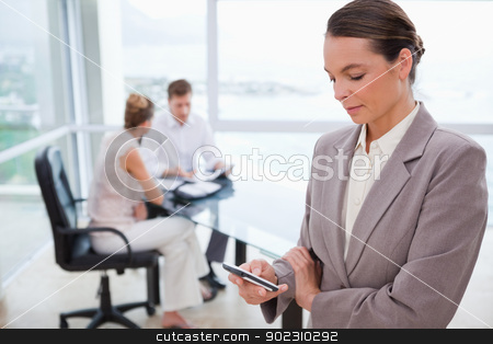 Standing real estate agent with cellphone stock photo, Standing real estate agent with cellphone and sitting clients behind her by Wavebreak Media