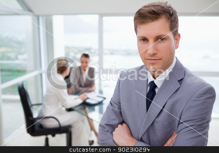 Young sales manager standing stock photo, Young sales manager standing with his team sitting behind him by Wavebreak Media