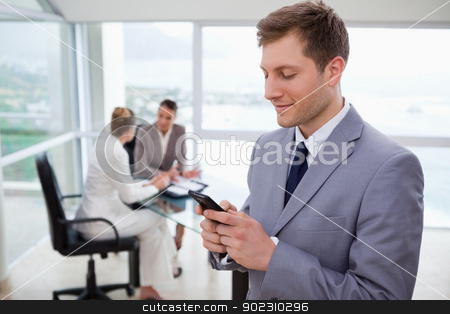 Sales manager writing text message stock photo, Sales manager writing text message with his team sitting behind him by Wavebreak Media