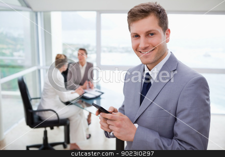 Sales manager holding cellphone stock photo, Sales manager holding cellphone with his team sitting behind him by Wavebreak Media