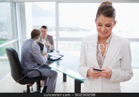 Marketing manager reading text message stock photo, Marketing manager reading text message with her team sitting behind her by Wavebreak Media