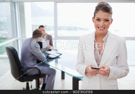 Smiling marketing manager holding cellphone stock photo, Smiling marketing manager holding cellphone with her team sitting behind her by Wavebreak Media