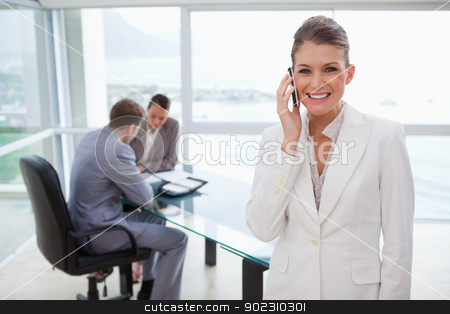 Smiling marketing manager on the phone stock photo, Smiling marketing manager on the phone with her team behind her by Wavebreak Media