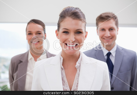Marketing manager standing stock photo, Marketing manager standing with her team behind her by Wavebreak Media