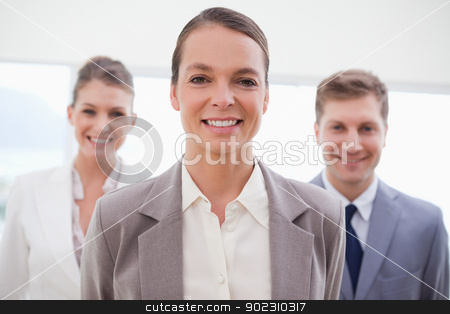 Business consultant with her team behind her stock photo, Business consultant standing with her team behind her by Wavebreak Media