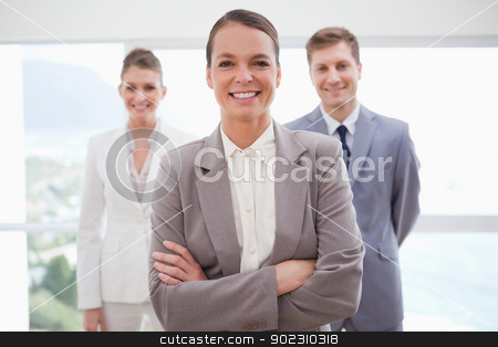 Business consultant with arms folded stock photo, Business consultant with arms folded and her team by Wavebreak Media
