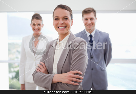 Smiling business consultant with arms folded stock photo, Smiling business consultant with arms folded together with her team by Wavebreak Media