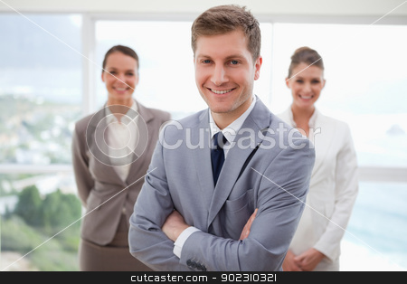Sales manager standing with arms folded stock photo, Sales manager standing with arms folded and his team behind him by Wavebreak Media