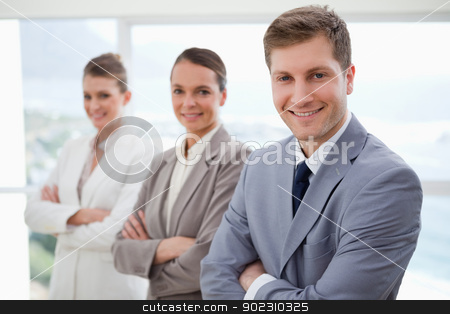 Business team standing with arms folded stock photo, Smiling business team standing with arms folded by Wavebreak Media