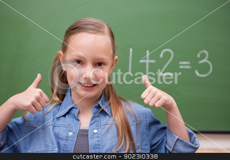 Schoolgirl with the thumbs up stock photo, Schoolgirl with the thumbs up in front of a backboard by Wavebreak Media
