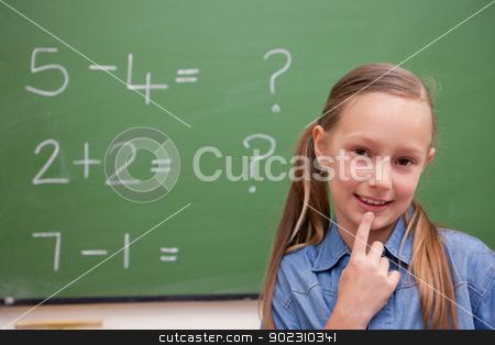 Cute schoolgirl thinking stock photo, Cute schoolgirl thinking in front of a blackboard by Wavebreak Media