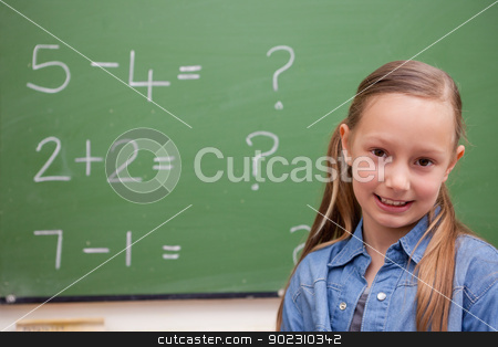 Cute schoolgirl posing stock photo, Cute schoolgirl posing in front of a blackboard by Wavebreak Media