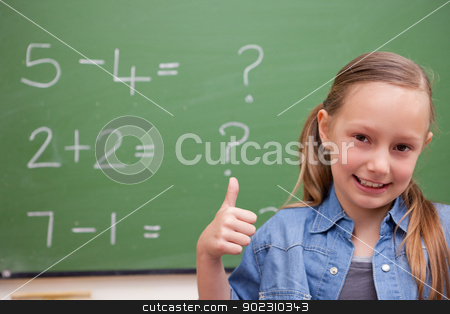 Schoolgirl with the thumb up stock photo, Schoolgirl with the thumb up in front of a blackboard by Wavebreak Media