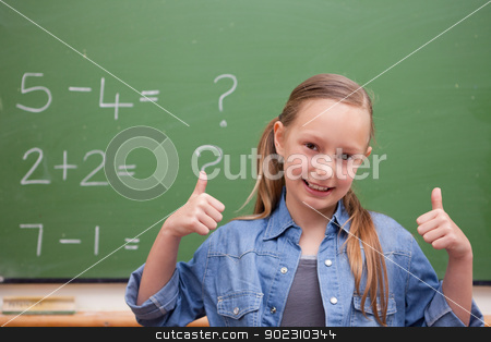 Smiling schoolgirl with the thumbs up stock photo, Smiling schoolgirl with the thumbs up in front of a blackboard by Wavebreak Media