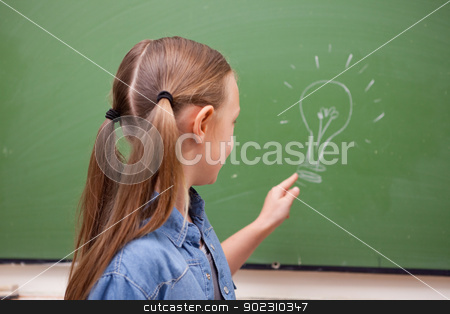 Schoolgirl pointing at a bulb stock photo, Schoolgirl pointing at a bulb on a blackboard by Wavebreak Media