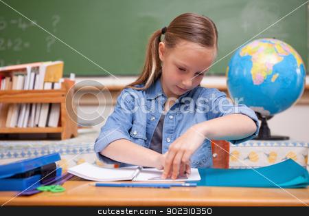 Schoolgirl doing classwork stock photo, Schoolgirl doing classwork looking away from the camera by Wavebreak Media