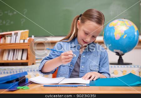 Smiling schoolgirl doing classwork stock photo, Smiling schoolgirl doing classwork looking away from the camera by Wavebreak Media
