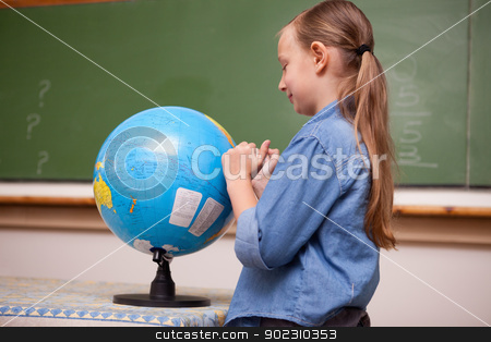 Schoolgirl looking at a globe stock photo, Schoolgirl looking at a globe in a classroom by Wavebreak Media