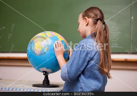 Focused schoolgirl looking at a globe stock photo, Focused schoolgirl looking at a globe in a classroom by Wavebreak Media