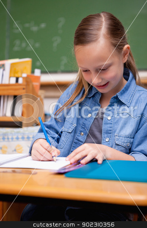Portrait of a schoolgirl writing stock photo, Portrait of a schoolgirl writing in a classroom by Wavebreak Media