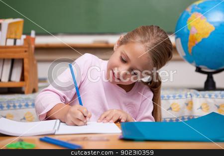 Happy schoolgirl writing stock photo, Happy schoolgirl writing in a classroom by Wavebreak Media