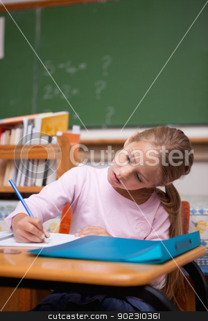 Portrait of a focused schoolgirl writing stock photo, Portrait of a focused schoolgirl writing in a classroom by Wavebreak Media