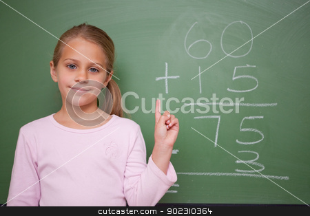 Cute schoolgirl raising her hand stock photo, Cute schoolgirl raising her hand in front of a blackboard by Wavebreak Media