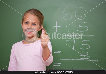 Cute schoolgirl with the thumb up stock photo, Cute schoolgirl with the thumb up in front of a blackboard by Wavebreak Media