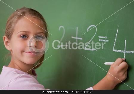 Smiling schoolgirl writing a number stock photo, Smiling schoolgirl writing a number in a blackboard by Wavebreak Media