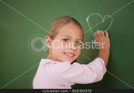Smiling schoolgirl drawing a heart stock photo, Smiling schoolgirl drawing a heart on a blackboard by Wavebreak Media