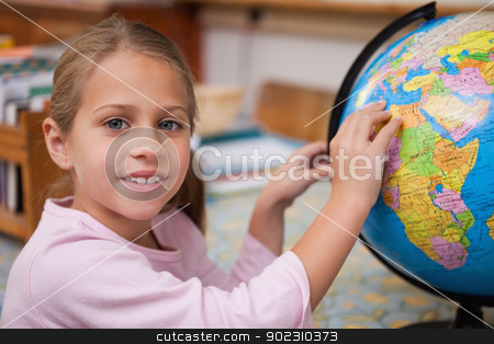 Schoolgirl pointing at a country stock photo, Schoolgirl pointing at a country on a globe by Wavebreak Media