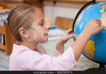 Smiling schoolgirl pointing at a country stock photo, Smiling schoolgirl pointing at a country on a globe by Wavebreak Media