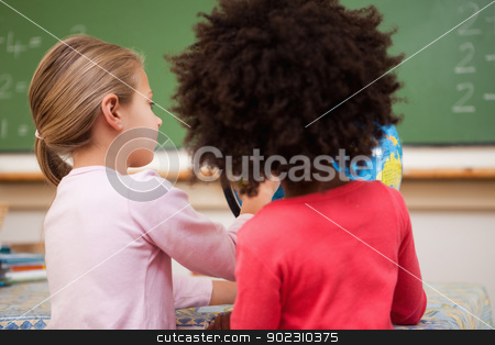 Schoolgirls looking at a globe stock photo, Schoolgirls looking at a globe in a classroom by Wavebreak Media