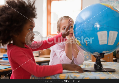 Happy schoolgirls looking at a globe stock photo, Happy schoolgirls looking at a globe in a classroom by Wavebreak Media
