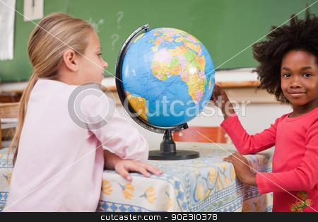 Cute schoolgirls looking at a globe stock photo, Cute schoolgirls looking at a globe in a classroom by Wavebreak Media