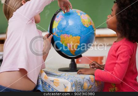Cute little schoolgirls looking at a globe stock photo, Cute little schoolgirls looking at a globe in a classroom by Wavebreak Media