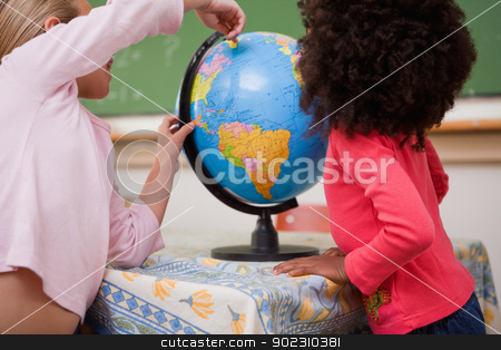 Schoolgirls pointing at a country stock photo, Schoolgirls pointing at a country on a globe by Wavebreak Media