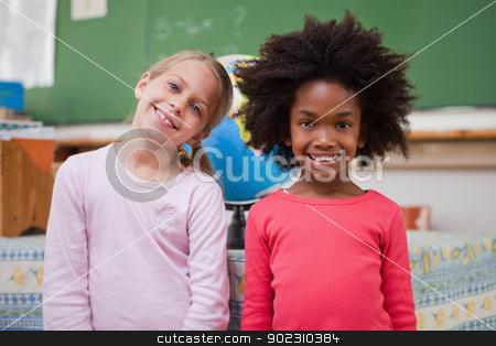 Cute schoolgirls posing stock photo, Cute schoolgirls posing in a classroom by Wavebreak Media