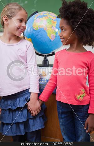 Portrait of smiling schoolgirls holding hands stock photo, Portrait of smiling schoolgirls holding hands in a classroom by Wavebreak Media
