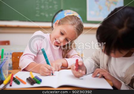 Cute schoolgirls drawing stock photo, Cute schoolgirls drawing in a classroom by Wavebreak Media