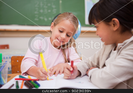 Smiling schoolgirls drawing stock photo, Smiling schoolgirls drawing in a classroom by Wavebreak Media
