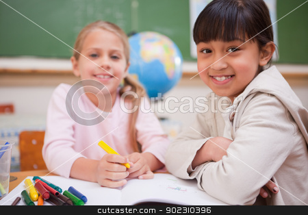 Smiling schoolgirls drawing while looking at the camera stock photo, Smiling schoolgirls drawing while looking at the camera in a classroom by Wavebreak Media
