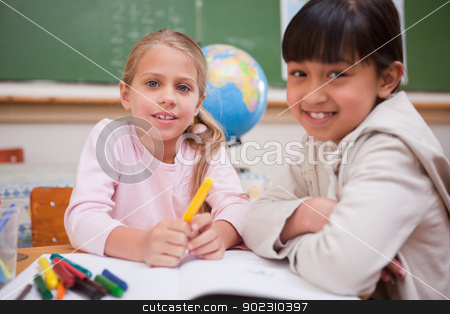 Schoolgirls drawing while looking at the camera stock photo, Schoolgirls drawing while looking at the camera in a classroom by Wavebreak Media