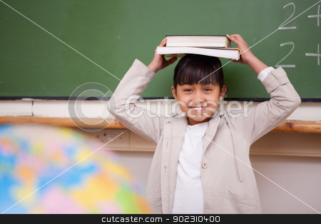 Schoolgirl holding her book on her head stock photo, Schoolgirl holding her book on her head in a classroom by Wavebreak Media