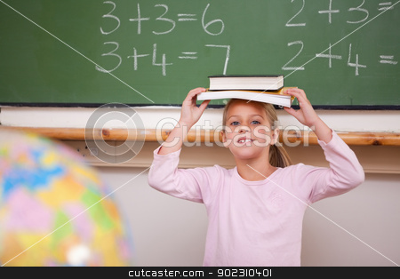 Smiling schoolgirl holding her book on her head stock photo, Smiling schoolgirl holding her book on her head in a classroom by Wavebreak Media