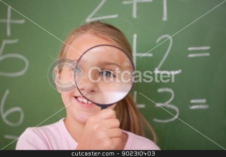 Schoolgirl looking through a magnifying glass stock photo, Schoolgirl looking through a magnifying glass against a blackboard by Wavebreak Media